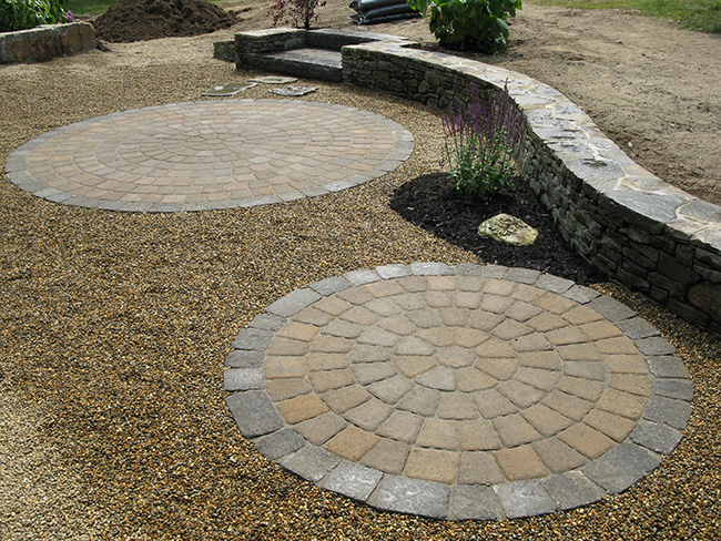 Circular patio with adjacent stone sitting wall in a Merricmack New Hampshire residential landscape