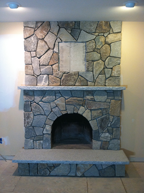 Field stone veneer customizes this fireplace for a home in Windham NH