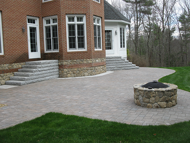 Large patio in Bedford New Hampshire with custom stone veneer fire pit