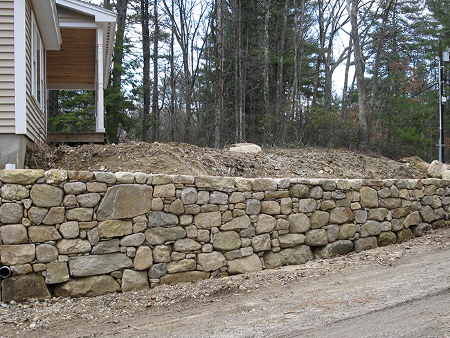 Large retaining wall in Bedford NH build by stone mason New England Accents