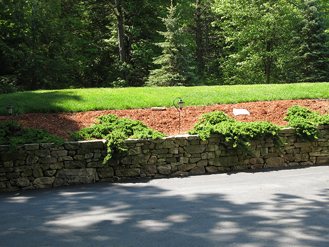 New England Accents built this stone retaining wall for landscaping client in New Boston NH