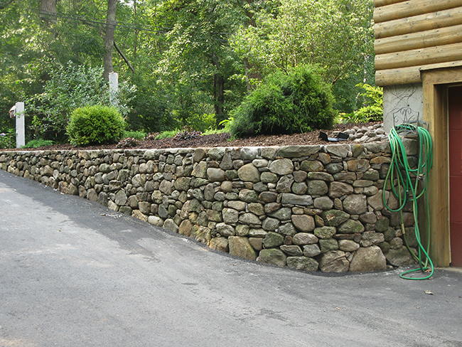Stone retaining wall in Goffstown NH by NEw England Accents professional stone masons