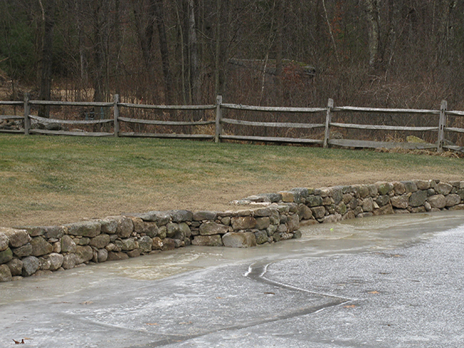 Stone wall beside a pond built by professional stone masons New England Accents